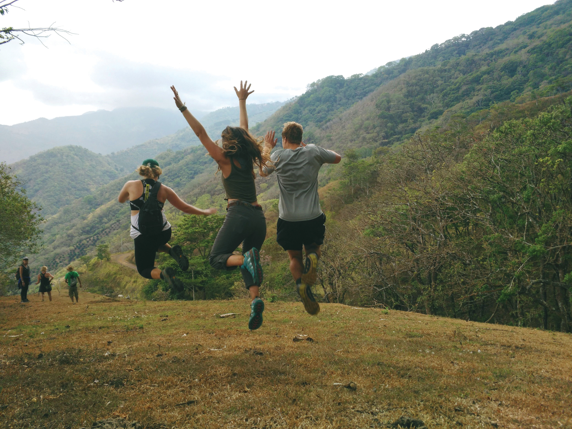 A group of students run and jump across the green hills of a Costa Rican countryside.
