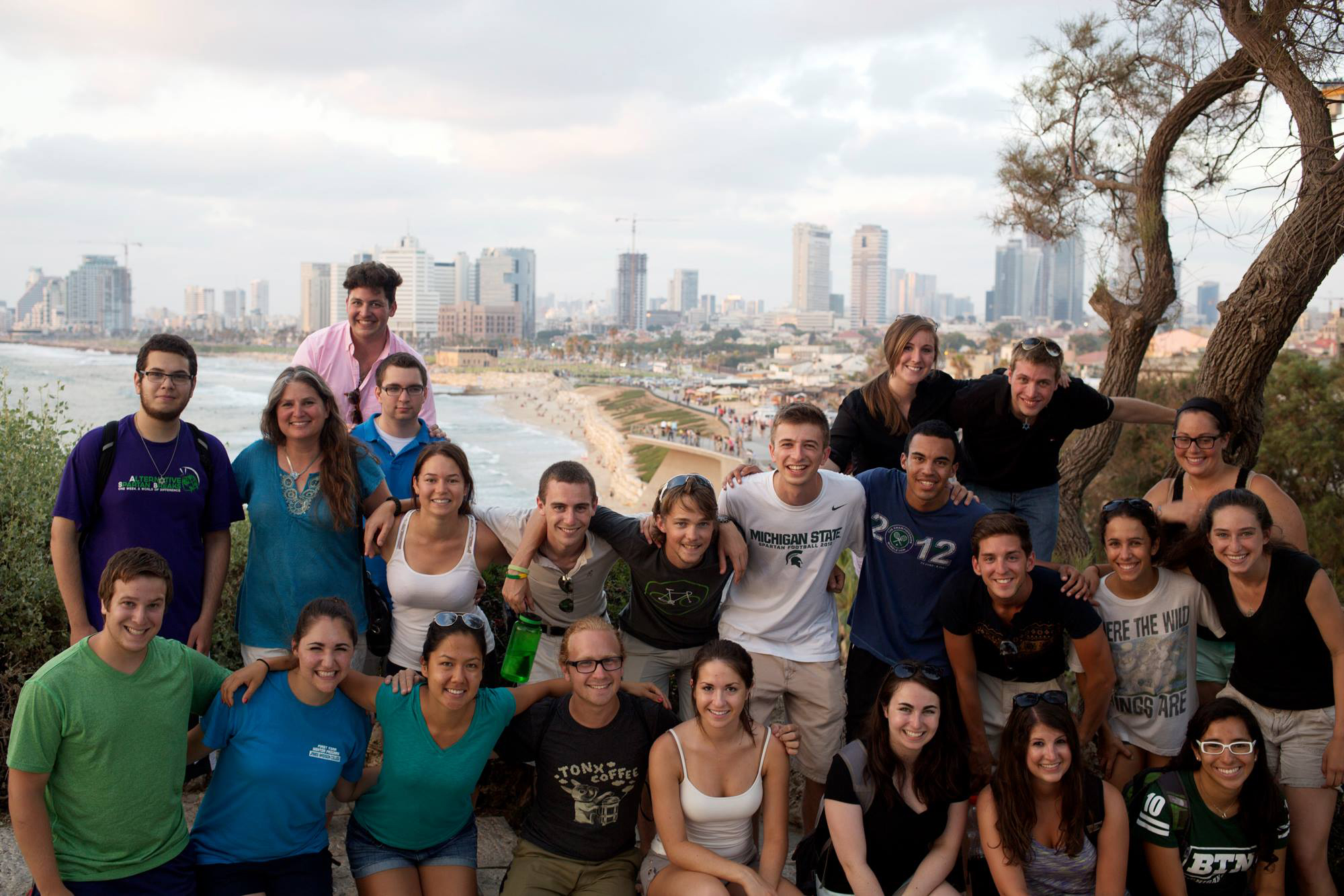 A diverse group of college students stand for a photo opportunity in Israel, the desert behind them.