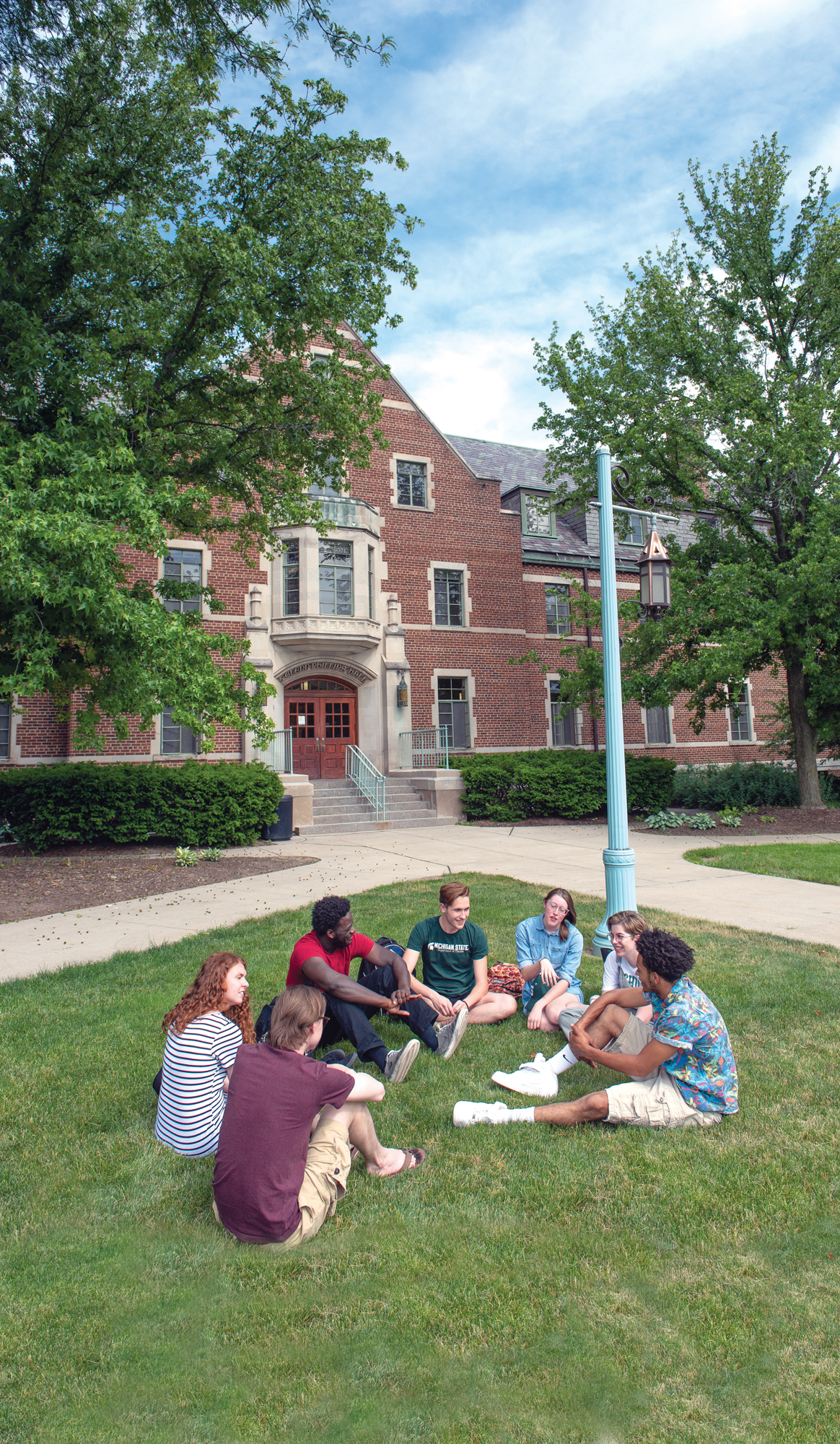 A diverse group of students sit outside in a circle in front of a brick building: Phillips Hall.