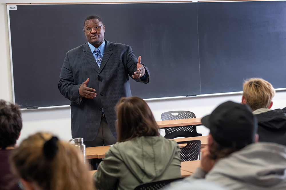 Professor Kevin Brooks, an african american professor, stands in front of his class in a suit and shares information with students.