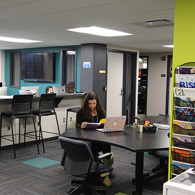 A view of the media center, with a student seated at a table and a row of computers behind a table in the background.
