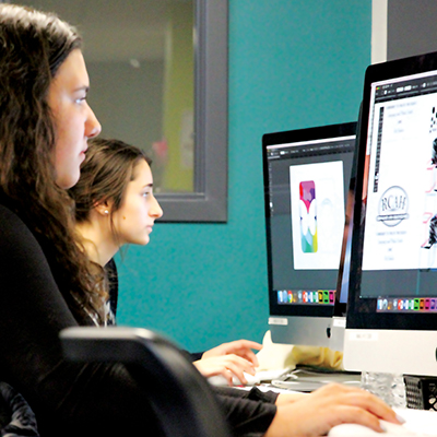 Two young women sit in front of computer screens, doing graphic design work in the media center.