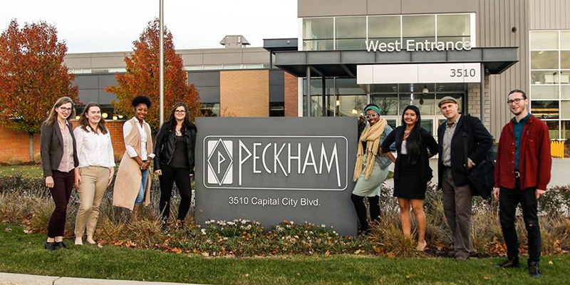 "RCAH students pose in front of a large, stone sign that reads ""Peckham"" on a fall day"