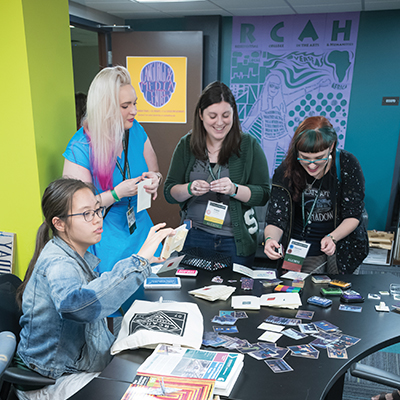 A diverse group of students stand around a table covered in stickers, making art.