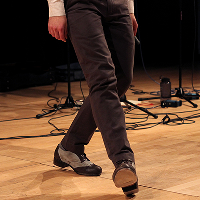 Tap dancing, cropped from waist down to show legs and shoes only on stage.