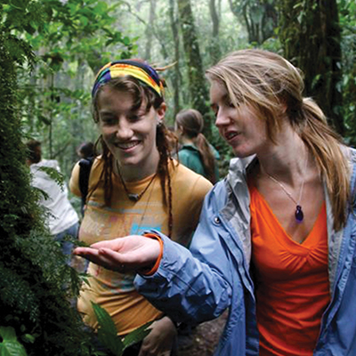 Two young women stand in the rainforest, examining moss on a tree.