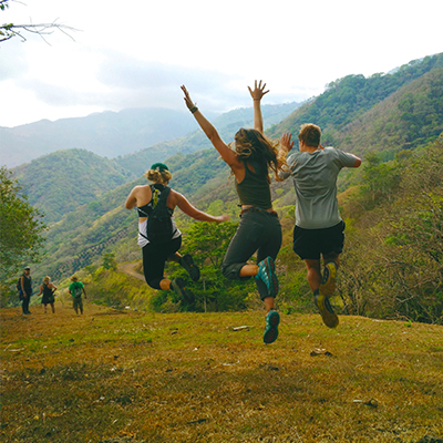 Three students in Costa Rica run and jump across a hilly, forested landscape.