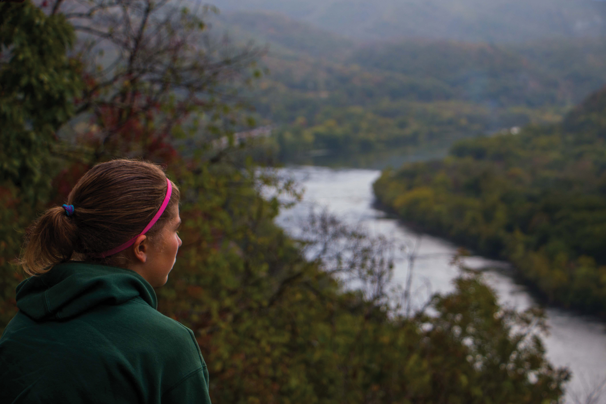A female student looks out over a vista of forested mountains in West Virginia.