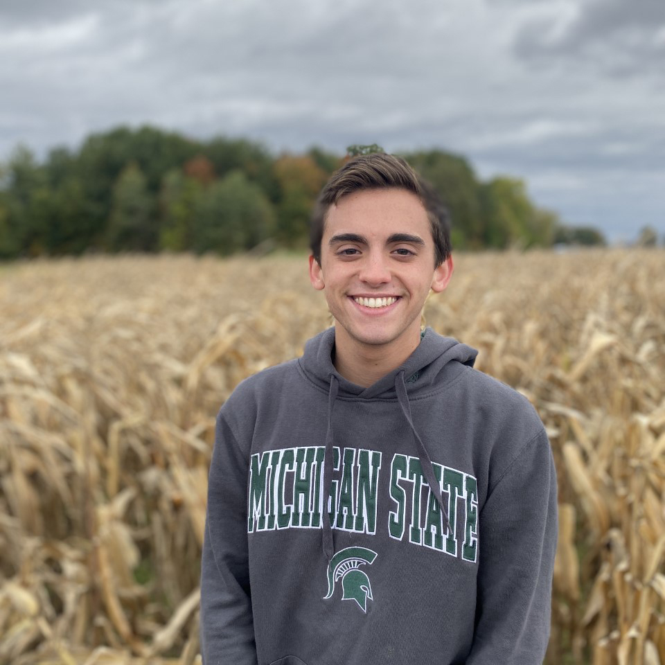 Image of a young man with dark hair standing in a field wearing a Spartan hoodie.