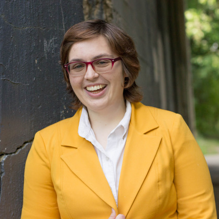 Image of a young woman with short dark hair wearing a bright yellow blazer.