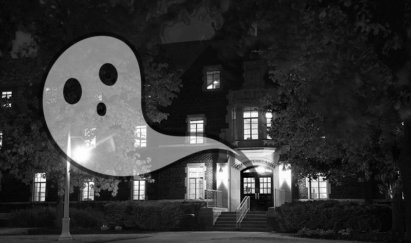 Image shows a brick building, Phillips Hall, at night lit up with every light on. A cartoonish ghost escapes from the doorway into the night.