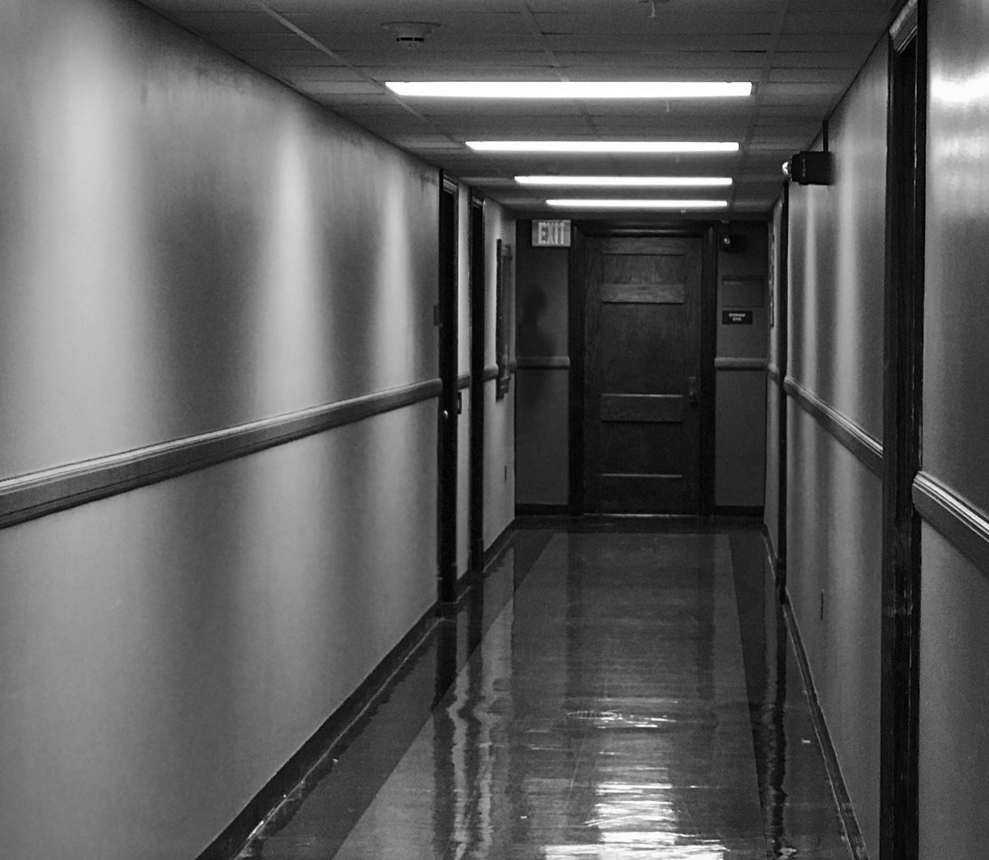 Image shows a hallway in a dorm room. At the end of the hallway is possibly a shadow person. Or photoshop.